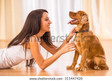 Happy woman is playing with a dog sitting on the floor at home.