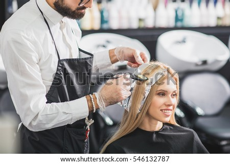 Happy woman is sitting at salon