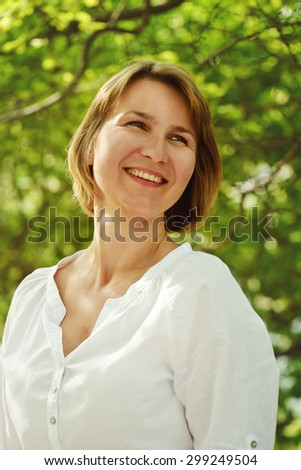 happy woman is smiling outdoors in summer time - stock photo