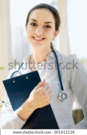 Happy woman is standing in the near window with folder