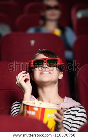 Happy woman is watching 3D movie - stock photo