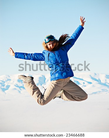 happy woman jumping against snowy mountains