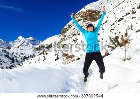 Happy woman jumping and cross country trail running in beautiful inspiring mountains landscape. Healthy lifestyle, fitness and exercising outdoors in winter nature. Inspiration and motivation. - stock photo