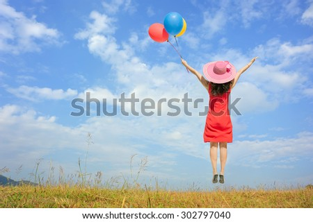 Happy Woman Jumping and holding balloon with blue sky outdoor.Summer Vacation concept