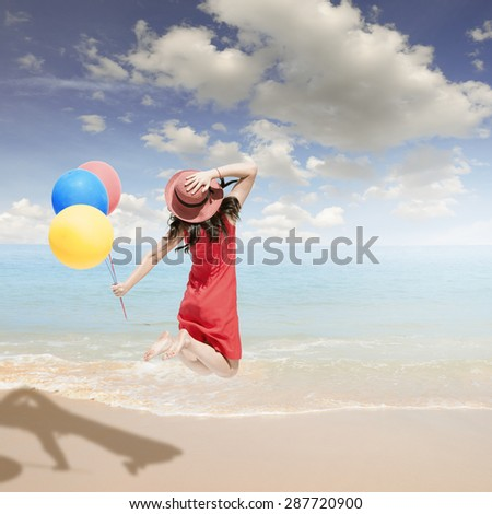Happy Woman jumping and holding balloons on the beach and clouds  sky.Summer holiday concept.