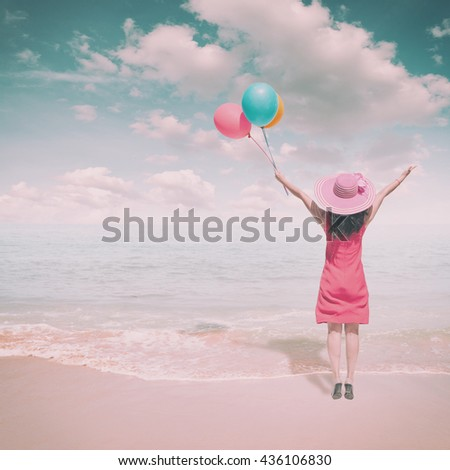 Happy Woman jumping and holding balloons on the beach and clouds sky.Summer holiday vacation concept.Vintage Tone - stock photo