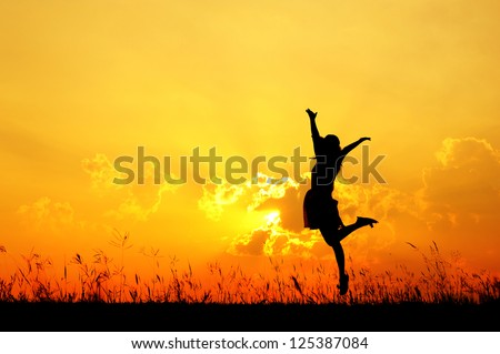 Happy woman jumping and sunset silhouette - stock photo