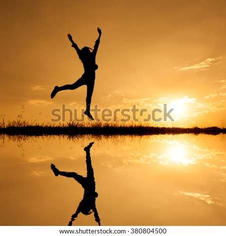 Happy  woman jumping and sunset silhouette,water reflect - stock photo