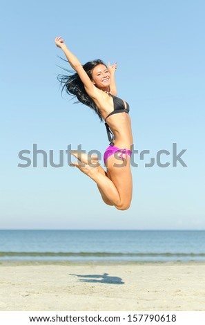 Happy woman jumping at the beach - stock photo