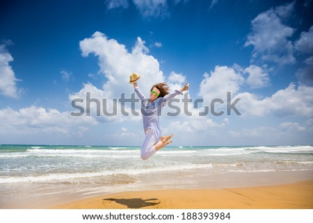 Happy woman jumping at the beach. Summer vacations and freedom concept - stock photo