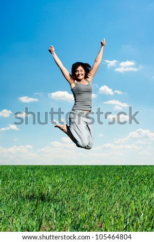 happy woman jumping at the field at sunny day - stock photo