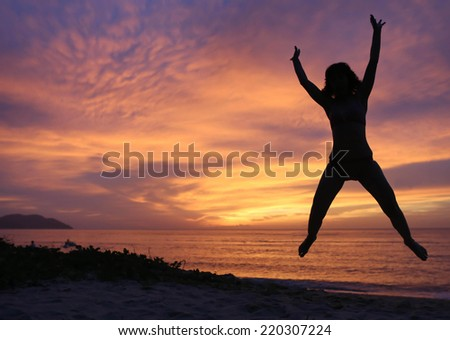 Happy Woman Jumping by the Sea at Sunset with copy space