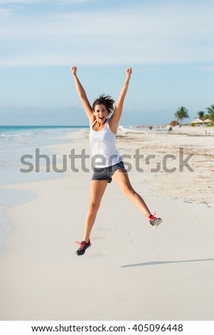 Happy woman jumping for celebrating workout success. Joyful sporty female exercising on caribbean beach. Fitness healthy lifestyle.