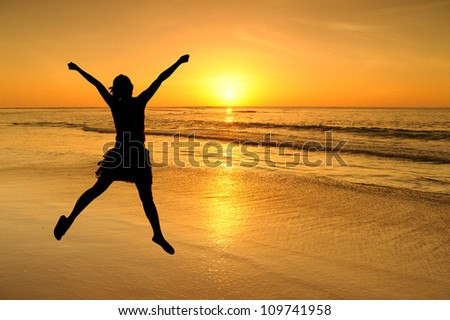 Happy Woman Jumping in beach and Sea Sunset