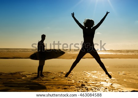 happy woman jumping in sea beach sunset silhouette. holiday vacation concept.