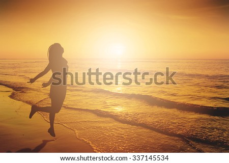 Happy Woman Jumping in Sea beach Sunset silhouette.Holiday vacation concept Copy space
