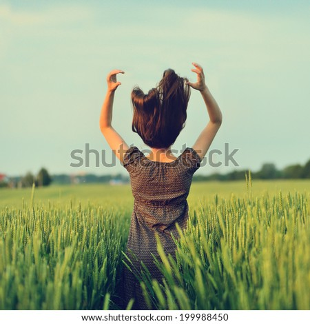 Happy woman jumping in the green field outdoor - stock photo