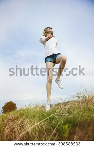 Happy woman jumping on meadow. Beautiful summer day on field.