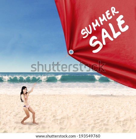 Happy woman jumping on the beach while pulling a banner of summer sale