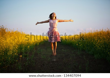 Happy woman jumps to the sky in the yellow meadow at the sunset - stock photo