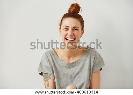 Happy woman Laughing. Closeup portrait woman smiling with perfect smile and white teeth looking laugh loudly isolated grey wall background. Positive human emotion facial expression body language.  - stock photo