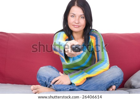 Happy woman laying on couch and watching television - stock photo