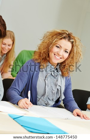Happy woman learning in study course and taking notes - stock photo
