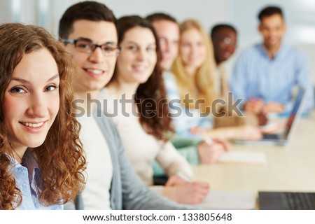 Happy woman learning in university seminar with other students