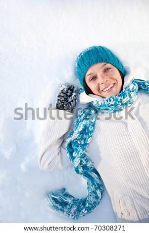 Happy woman lies in snow - stock photo