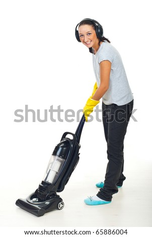 Happy woman listening music in headphones and working with vacuum cleaner on white wooden floor - stock photo