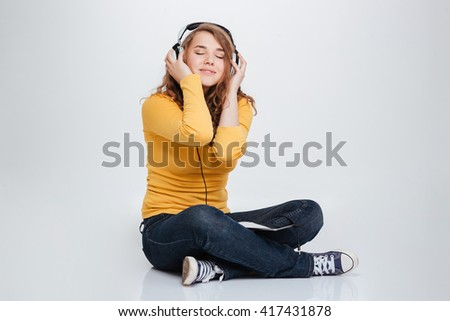 Happy woman listening music in headphones isolated on a white background - stock photo