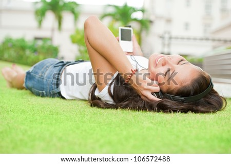 Happy woman listening to music in the park