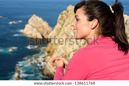 Happy woman looking at beautiful coast landscape and sea. Brunette tourist enjoying peace and relax on summer vacation travel sunny day. Cabo de Pe�±as, Asturias, Spain. - stock photo