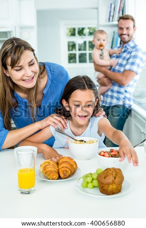 Happy woman looking at daughter having breakfast in kitchen at home with family in background