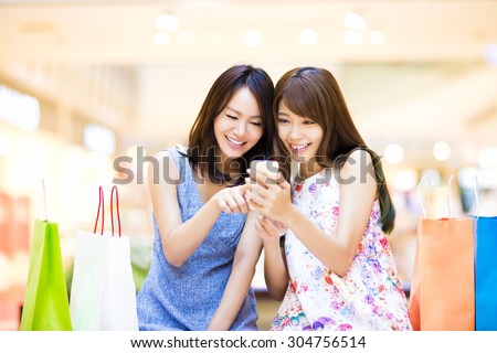 Happy woman looking at smart phone at  shopping mall - stock photo