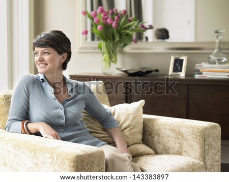 Happy woman looking away while sitting on armchair in house