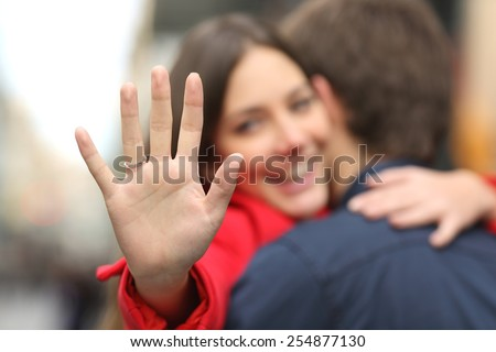 Happy woman looking engagement ring after proposal while is cuddling her boyfriend in the street - stock photo