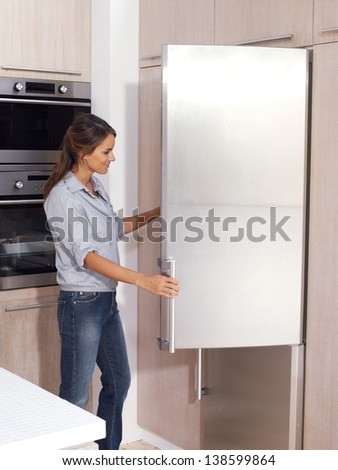 Happy woman looking for something in the fridge at home - stock photo