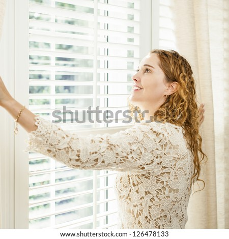 Happy woman looking out big bright window with curtains and blinds