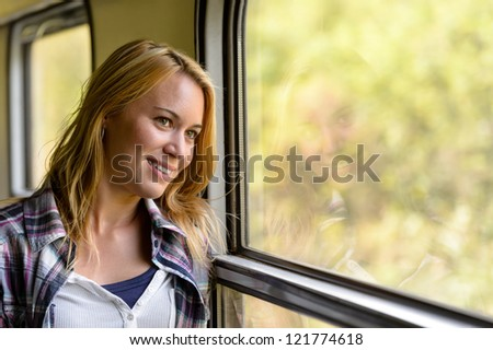 Happy woman looking out train window pensive vacation traveling tourist - stock photo