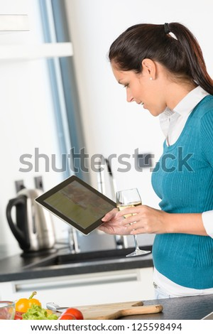 Happy woman looking recipe tablet kitchen reading cooking - stock photo