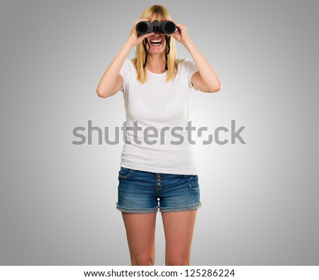 happy woman looking through binoculars against a grey background - stock photo