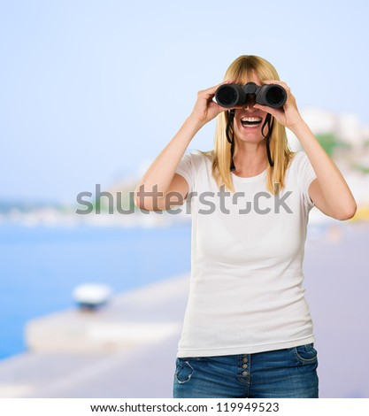 happy woman looking through binoculars at a port