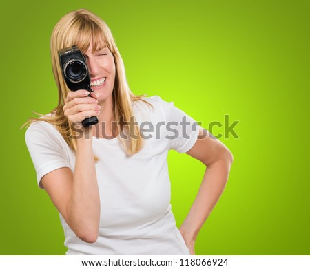 Happy Woman Looking Through Camera against a green background - stock photo