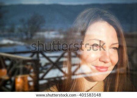 happy woman looking through window on mountain landscape - stock photo
