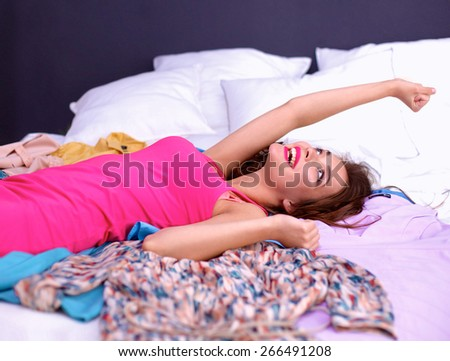 Happy woman lying bed surrounded by her clothes - stock photo