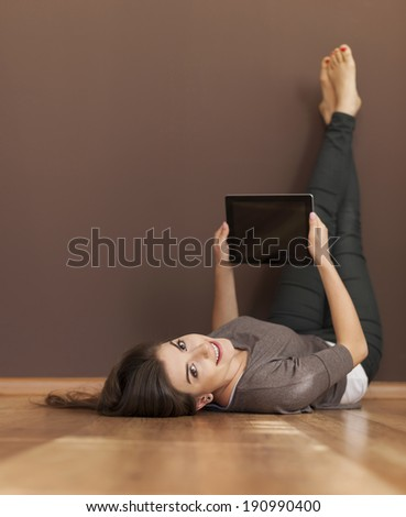Happy woman lying on floor with digital tablet