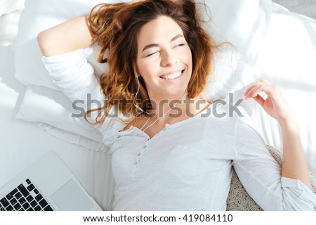 Happy woman lying on the bed and waking up in the morning - stock photo