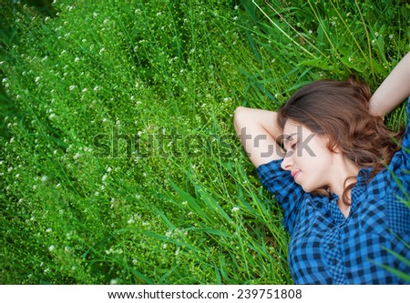 happy woman lying on the grass and dreaming. - stock photo
