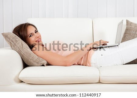 Happy Woman Lying On The Sofa With Laptop.